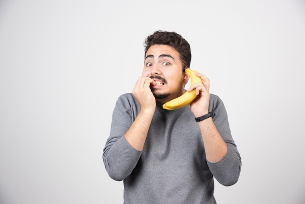 A young man model holding a banana as a phone.