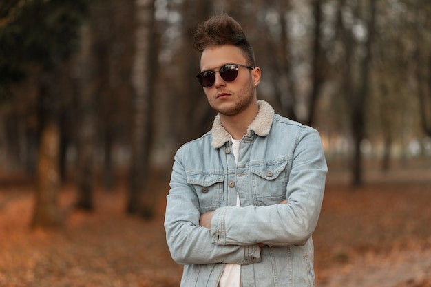公園でポーズをとるスタイリッシュなデニムの青いジャケットの若い男のモデル