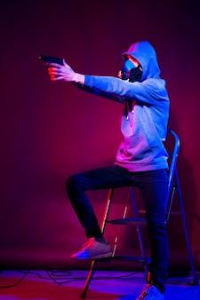Модель молодого человека позирует в студии в модном неоновом свете в спортивном костюме, капюшоне и маске, держащей пистолет.