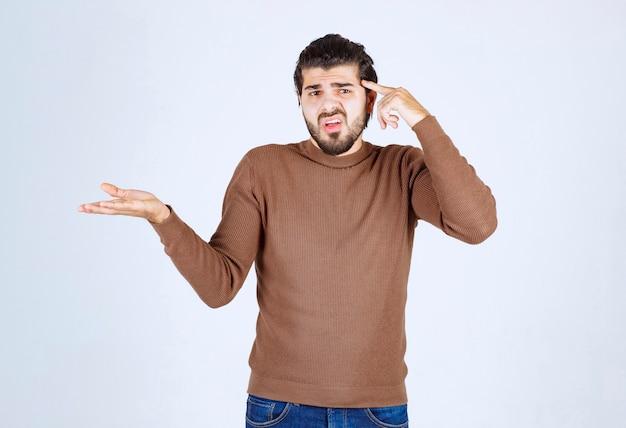 Модель молодого человека показывая руку и указывая на его голову.