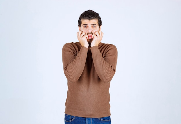 若い男のモデルは、顔の近くに立って手をつないでいます。