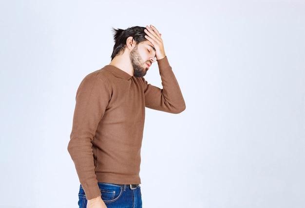 젊은 남자 모델 서서 고통으로 고통받는 머리를 잡고.