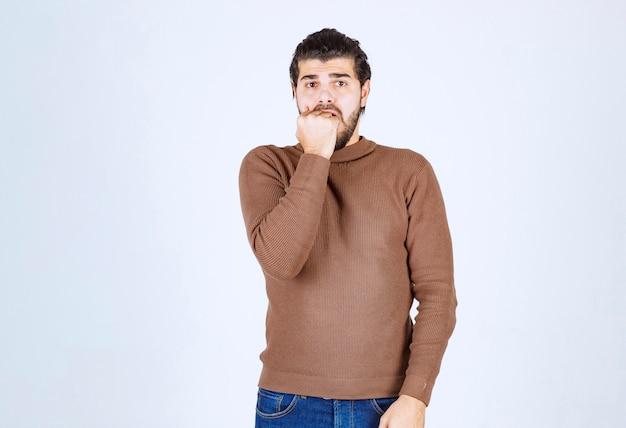 A young man model standing and biting his nails over white wall .