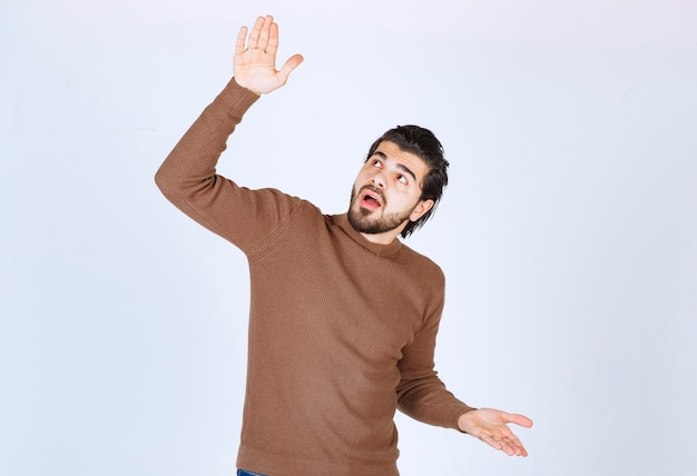 Un modello di giovane uomo in piedi e alzando lo sguardo con le mani aperte. foto di alta qualità