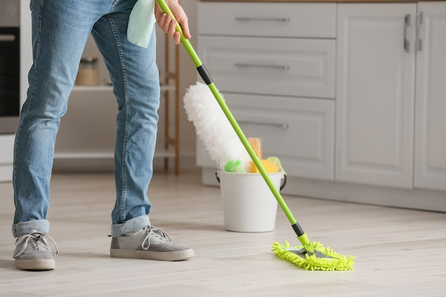 Young man mopping floor in kitchen