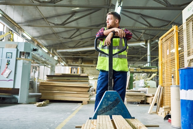 Young man moving boards in warehouse