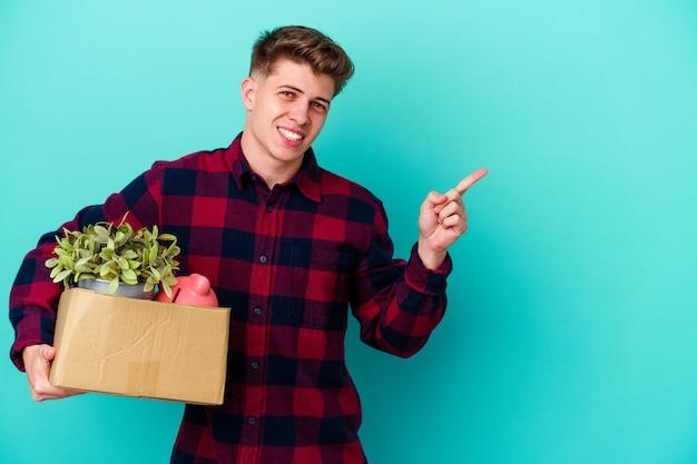 웃 고 옆으로 가리키는 파란색 벽에 고립 된 상자를 들고 이동하는 젊은 남자, 빈 공간에서 뭔가 보여주는