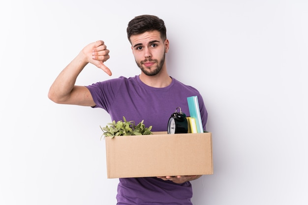 Young man moving a new home isolated showing a dislike gesture, thumbs down