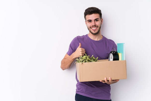 Young man moving a new home isolated smiling and raising thumb up