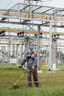 A young man mowing grass on the territory of an electric substation in overalls. grass cleaning at the enterprise, implementation of fire safety measures.
