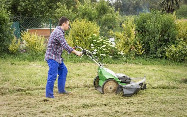 잔디 깎는 기계로 잔디를 깎는 청년