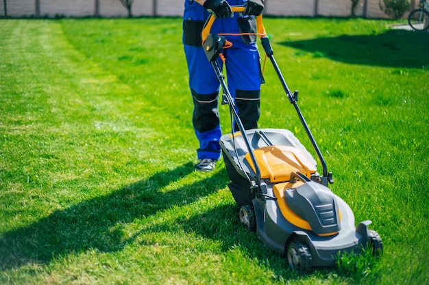 Young man mows the lawn using an electric lawn mower in a special worker suit near a large country house in the backyard