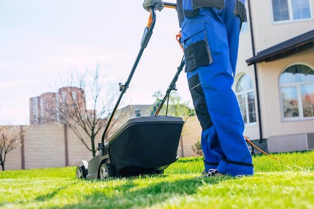若い男は裏庭の大きなカントリーハウスの近くで特別な労働者のスーツで電動芝刈り機を使用して芝生を刈り取ります