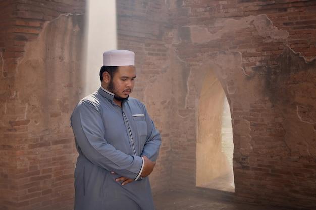 Young man muslim praying at an old mosque in ayutthaya, thailand