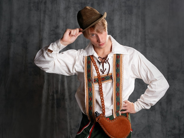 A young man in a national bavarian suit with shorts on suspenders and a hat. charismatic bavarian greets with a nod of his head, photo in the studio on a gray background
