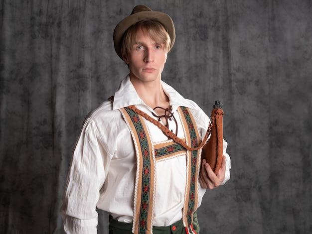 A young man in a national bavarian suit with shorts on suspenders and a hat.