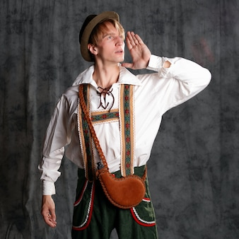 A young man in a national bavarian suit with shorts on suspenders and a hat