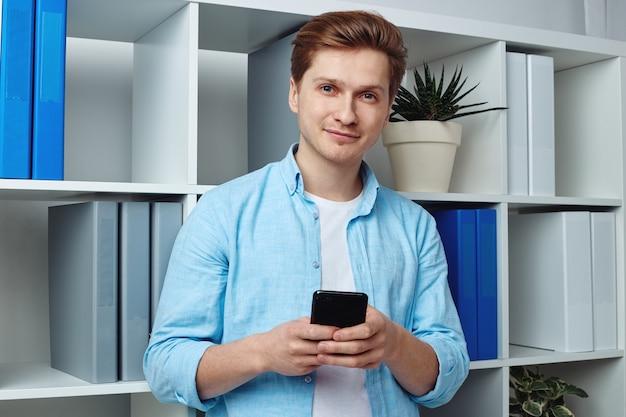 Молодой человек перемещается в своем смартфоне, стоя в офисе