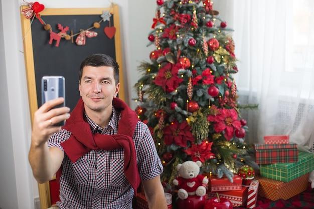 편안한 옷을 입고 집에서 크리스마스 트리 근처 젊은 남자가 스마트 폰 화면 앞에서 안녕 / 작별 인사의 표시로 손을 흔들고 있습니다. 크리스마스와 새해 영상 연결을 축하합니다.