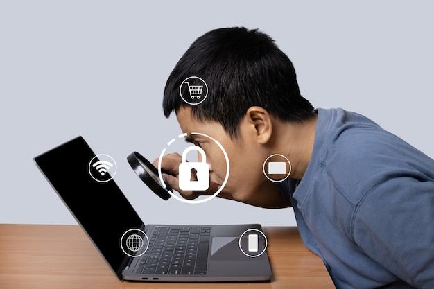 ロックアイコンセキュリティ技術を備えた虫眼鏡でラップトップを観察している若い男。