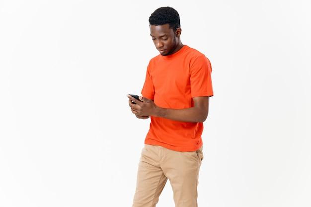 밝은 배경에 휴대전화와 주황색 티셔츠를 입은 아프리카 외모의 청년