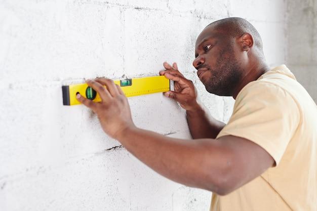 Молодой человек африканской национальности прикладывает ручной инструмент для измерения уровня к выкрашенной в белый цвет кирпичной стене, проверяя ее плоскостность во время ремонта дома