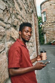 휴대 전화에서 스크롤 하 고 음료를 마시는 아프리카 민족의 젊은 남자