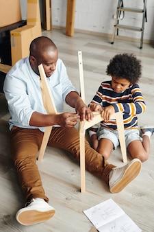 新しいアパートや家の床に座って新しい家具を組み立てる方法を彼のかわいい幼い息子に教えるアフリカ民族の若い男