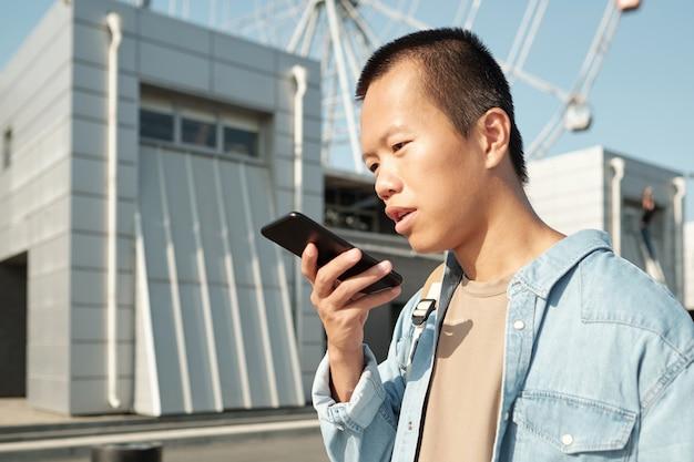 음성 메시지를 녹음하는 아시아 민족의 젊은 남자
