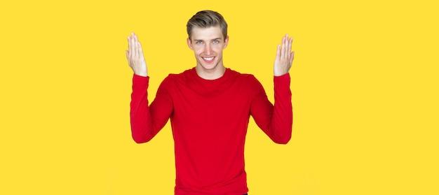 Молодой человек европейской внешности на желтом фоне. доверительная улыбка поднимает раскрытые ладони вверх. копировать пространство