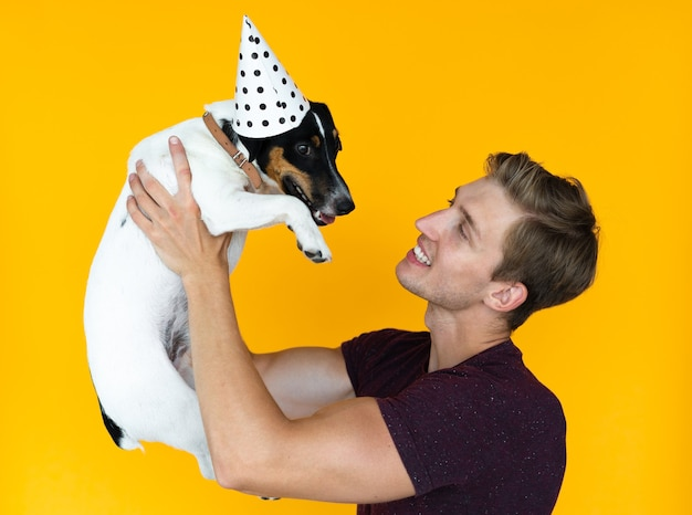 黄色の背景にヨーロッパの外観の若い男。犬のジャックラッセルを持ってお互いを見つめている