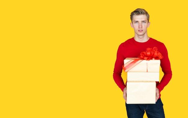 黄色の背景にヨーロッパの外観の若い男。ギフト付きの箱を保持します。コピースペース