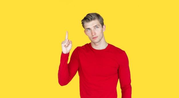 Молодой человек европейской внешности на желтом фоне. поднимает указательный палец одной руки вверх. копировать пространство