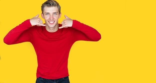 노란색 바탕에 유럽풍의 젊은 남자. 전화를 시뮬레이션하는 두 손을 올립니다. 복사 공간