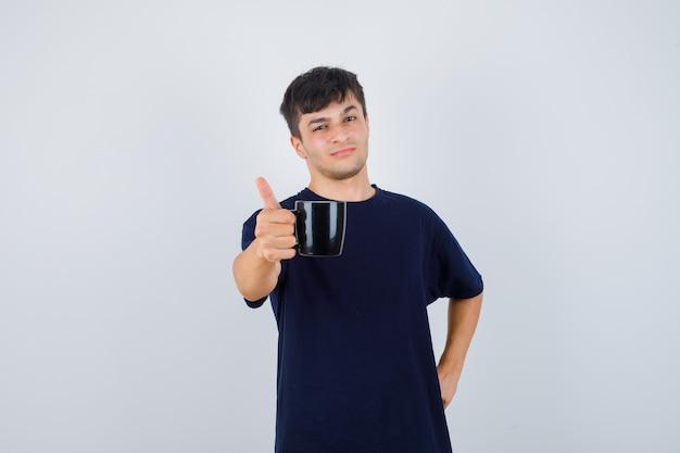 검은 티셔츠에 커피 한 잔을 제공하고 자랑스럽게 보이는 젊은 남자. 전면보기.
