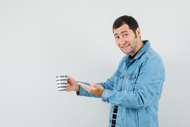 T- 셔츠, 재킷 및 유쾌한 찾고 음료 한잔 제공하는 젊은 남자.