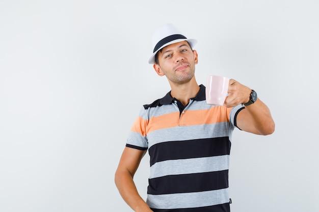 Молодой человек предлагает чашку чая в футболке и шляпе и выглядит вежливо