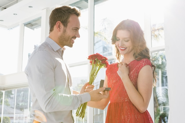 Young man offering flowers and engagement ring to beautiful woman