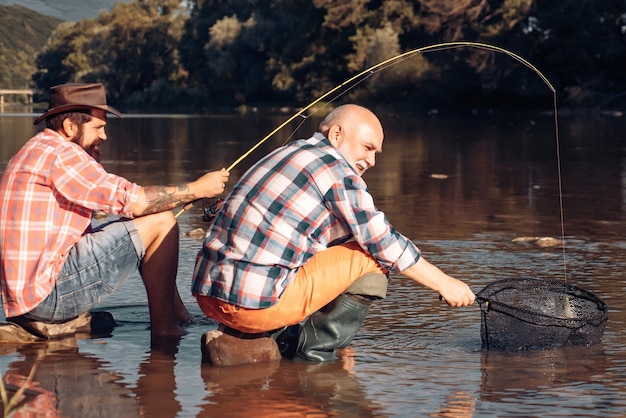 Young man and old mature man fly fishing. man fishing and relaxing while enjoying hobby. portrait of