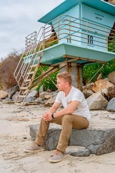 Молодой человек на красивом пляже с синей спасательной шлюпкой в сан-элихо стейт-бич сан-диего