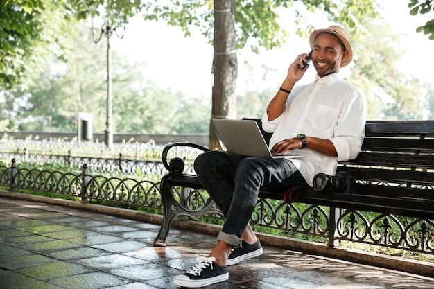 Молодой человек на скамейке с ноутбуком и камерой, разговаривает со смартфоном