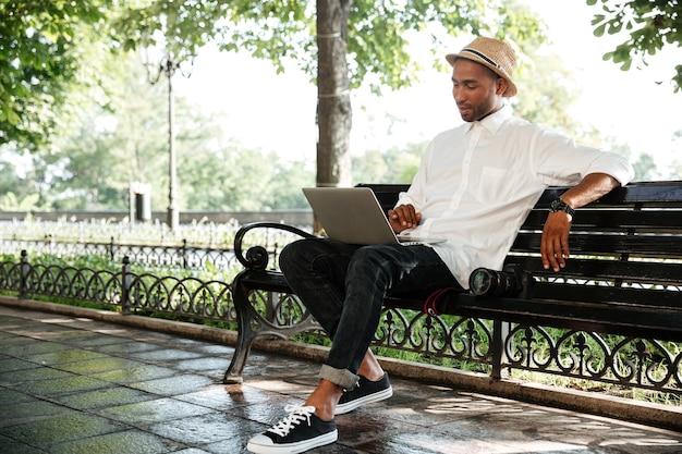 Молодой человек на скамейке с ноутбуком и камерой