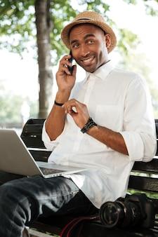 Молодой человек на скамейке с ноутбуком, смартфоном и камерой