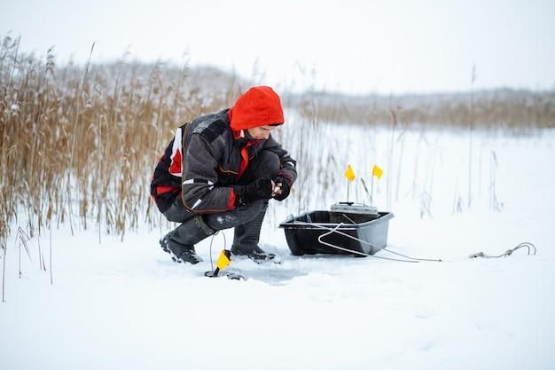 Молодой человек на заснеженном озере зимой рыбак устанавливает наживку