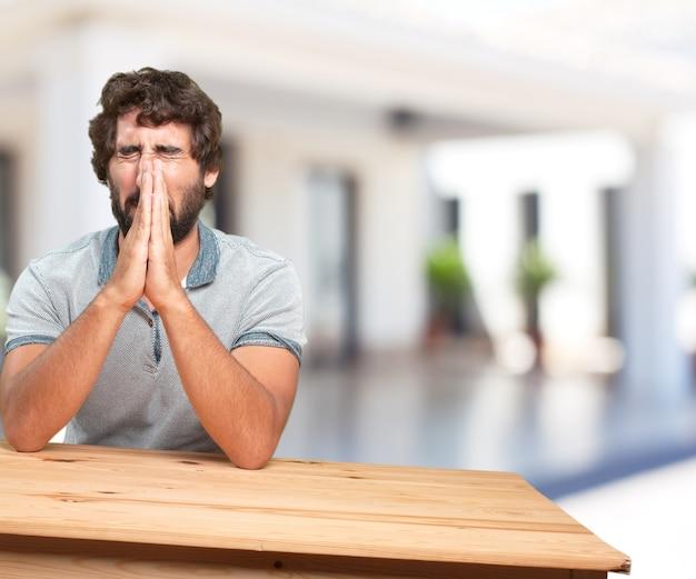 테이블에 젊은 남자. 걱정스러운 표현