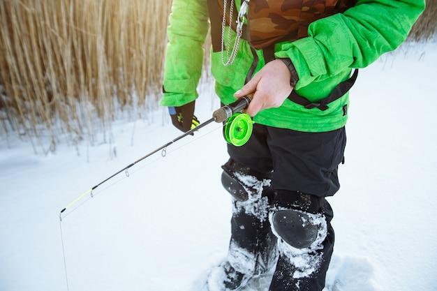 Молодой человек на зимней рыбалке на заснеженном озере ловит рыбу на удочке