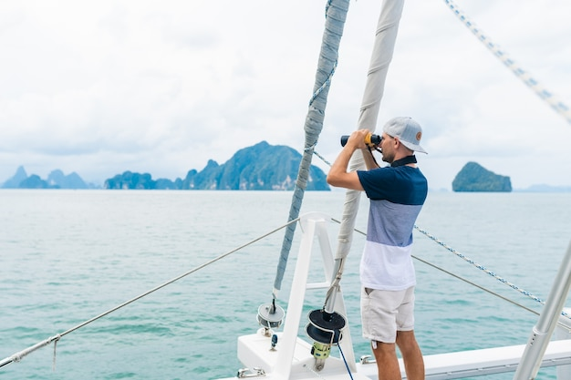双眼鏡で見ているヨットの若い男