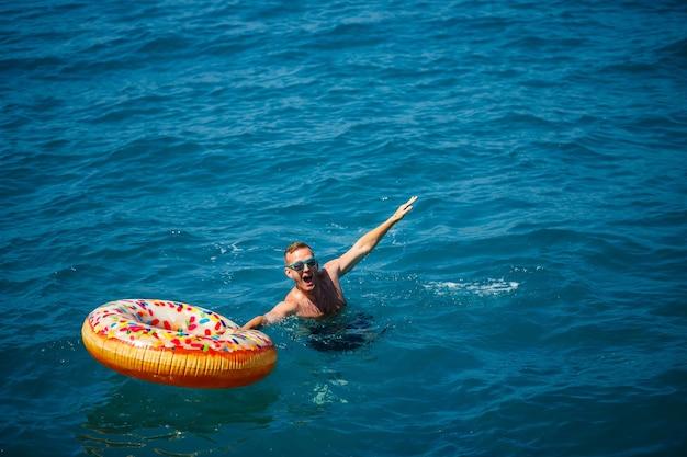 Молодой человек на надувном кольце в море отдыхает и купается в солнечный день