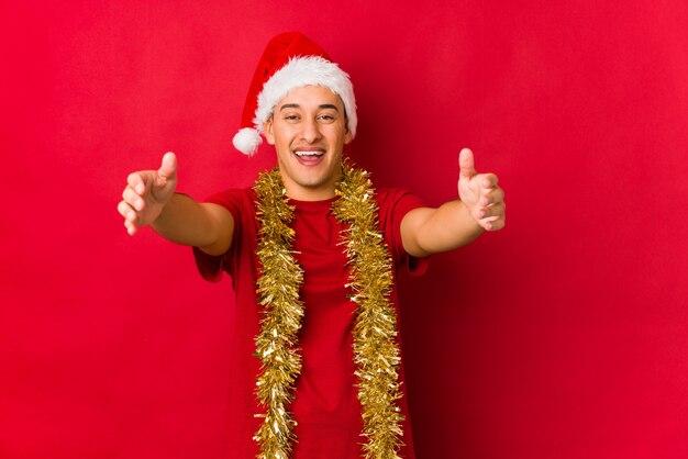 クリスマスの日の若い男は、カメラに抱擁を与えると確信しています。