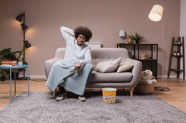 Молодой человек на диване, смотреть телевизор